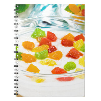 Oatmeal with colorful candied fruits in a glass notebook