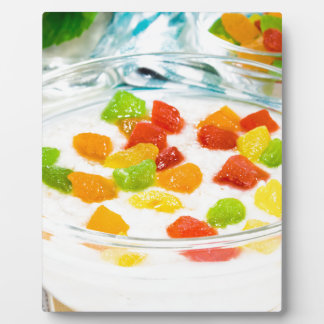 Oatmeal with colorful candied fruits in a glass plaque