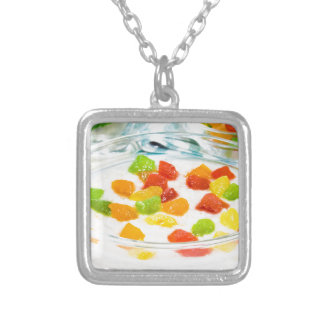 Oatmeal with colorful candied fruits in a glass silver plated necklace