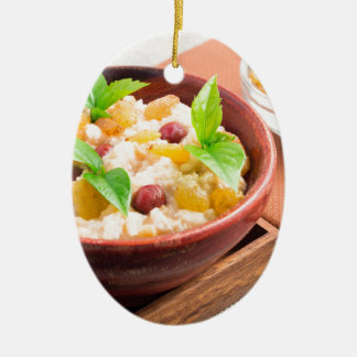 Oatmeal with raisins and berries in a wooden bowl ceramic ornament