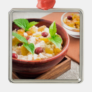 Oatmeal with raisins and berries in a wooden bowl Silver-Colored square decoration