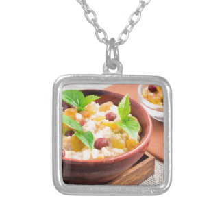 Oatmeal with raisins and berries in a wooden bowl silver plated necklace