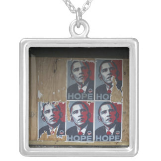 Obama signs in a boarded window of a closed square pendant necklace
