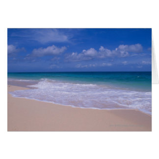 Ocean waves foaming onto sandy beach card