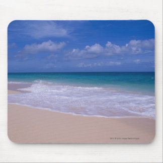 Ocean waves foaming onto sandy beach mouse pad