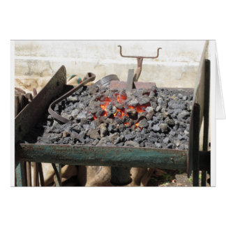 Old-fashioned blacksmith furnace . Burning coals Card