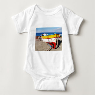 Old fishing boat drawn up on pavement. baby bodysuit