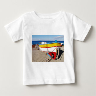 Old fishing boat drawn up on pavement. tee shirt