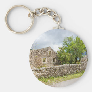 Old historic house as ruins along road basic round button key ring