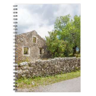 Old historic house as ruins along road notebook