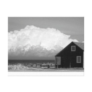 Old little house facing huge stormy clouds canvas print