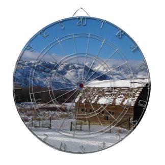 Old mountain farm in winter dartboard with darts