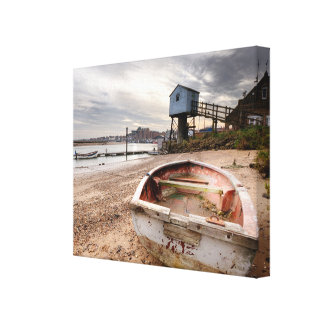Old red rowing boat on the beach with tower canvas print