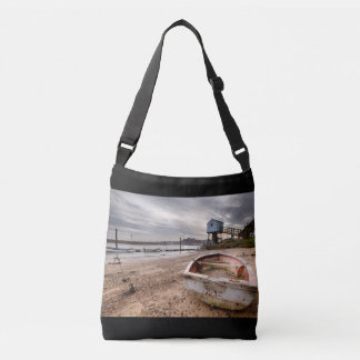 Old rowing boat and lookout tower on beach crossbody bag