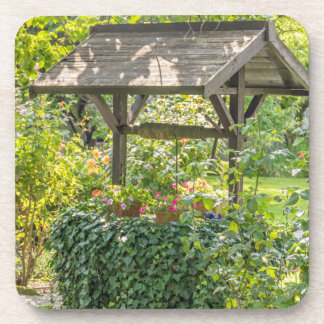 Old well in a garden hard plastic coasters