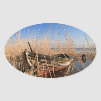 Old wooden boat in the reeds oval sticker