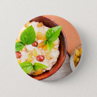 Old wooden bowl of healthy oatmeal with berries 6 cm round badge