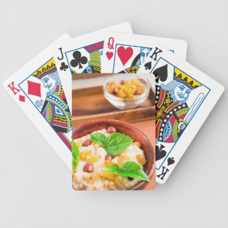 Old wooden bowl of healthy oatmeal with berries bicycle playing cards