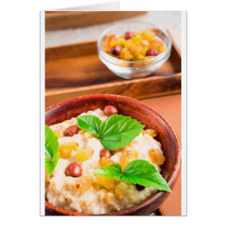 Old wooden bowl of healthy oatmeal with berries card