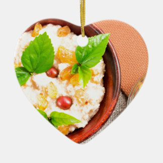 Old wooden bowl of healthy oatmeal with berries ceramic heart decoration