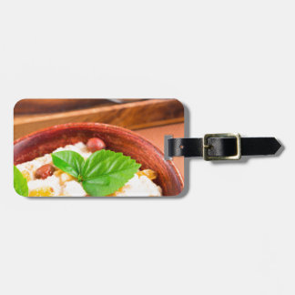 Old wooden bowl of healthy oatmeal with berries luggage tag
