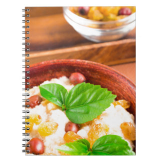 Old wooden bowl of healthy oatmeal with berries spiral notebook
