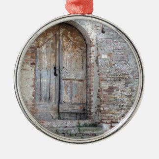 Old wooden door in old brick wall metal ornament
