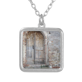 Old wooden door in old brick wall silver plated necklace