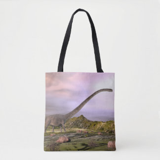 Omeisaurus walking in the desert by sunset tote bag