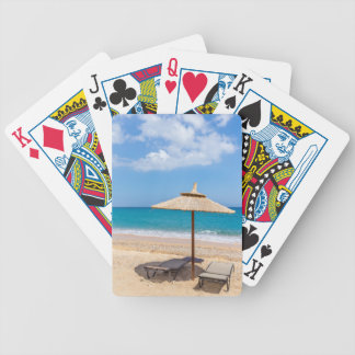 One beach umbrella and sunloungers near ocean bicycle playing cards