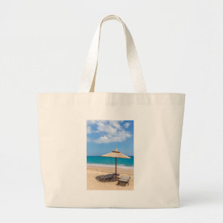 One beach umbrella and sunloungers near ocean large tote bag