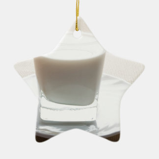 One glass of milk on a white saucer in backlit ceramic star decoration