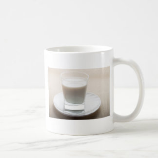 One glass of milk on a white saucer in backlit coffee mug