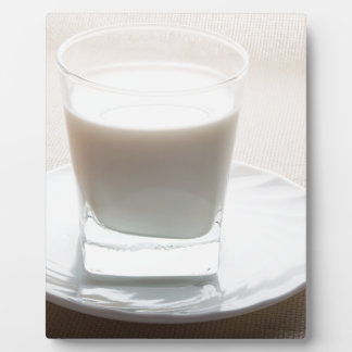One glass of milk on a white saucer in backlit plaque