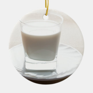 One glass of milk on a white saucer in backlit round ceramic decoration