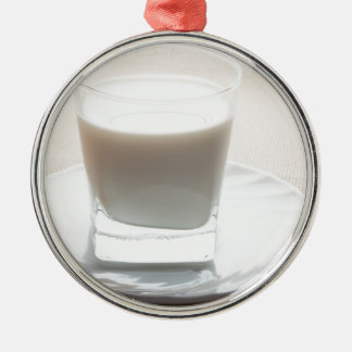 One glass of milk on a white saucer in backlit Silver-Colored round decoration
