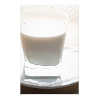 One glass of milk on a white saucer in backlit stationery