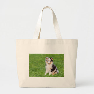 One young sheltie dog sitting on grass large tote bag