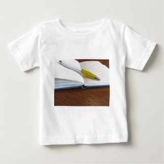 Opened blank lined notebook with pen baby T-Shirt