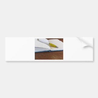 Opened blank lined notebook with pen bumper sticker