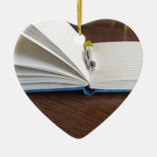 Opened blank lined notebook with pen ceramic heart decoration