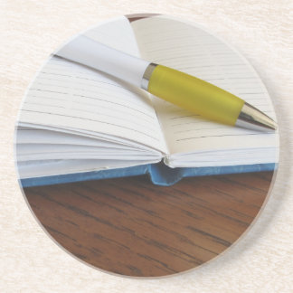 Opened blank lined notebook with pen coaster
