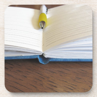 Opened blank lined notebook with pen coasters