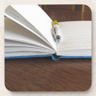 Opened blank lined notebook with pen drink coasters