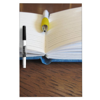 Opened blank lined notebook with pen Dry-Erase boards