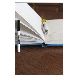 Opened blank lined notebook with pen dry erase boards
