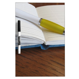 Opened blank lined notebook with pen dry erase whiteboard