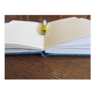 Opened blank lined notebook with pen postcard