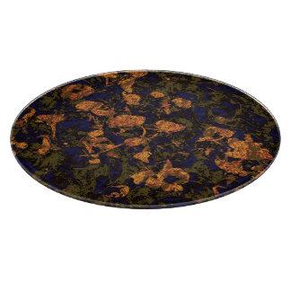 Orange flower against leaf camouflage pattern cutting board