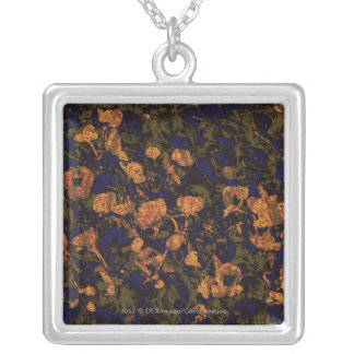 Orange flower against leaf camouflage pattern jewelry